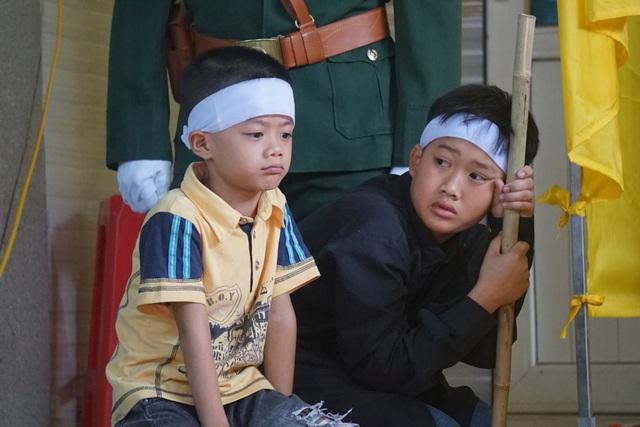 Hai con trai lớn của anh cũng ngẩn ngơ nhìn linh cữu cha, rồi lại nhìn người lớn trong nhà.