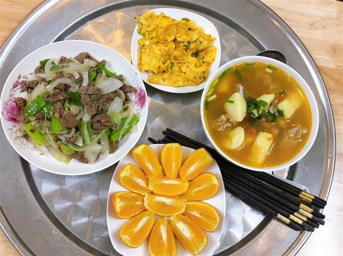 Canh khoai tây hầm xương, thịt bò xào hành tây, trứng chiên, cam tươi.