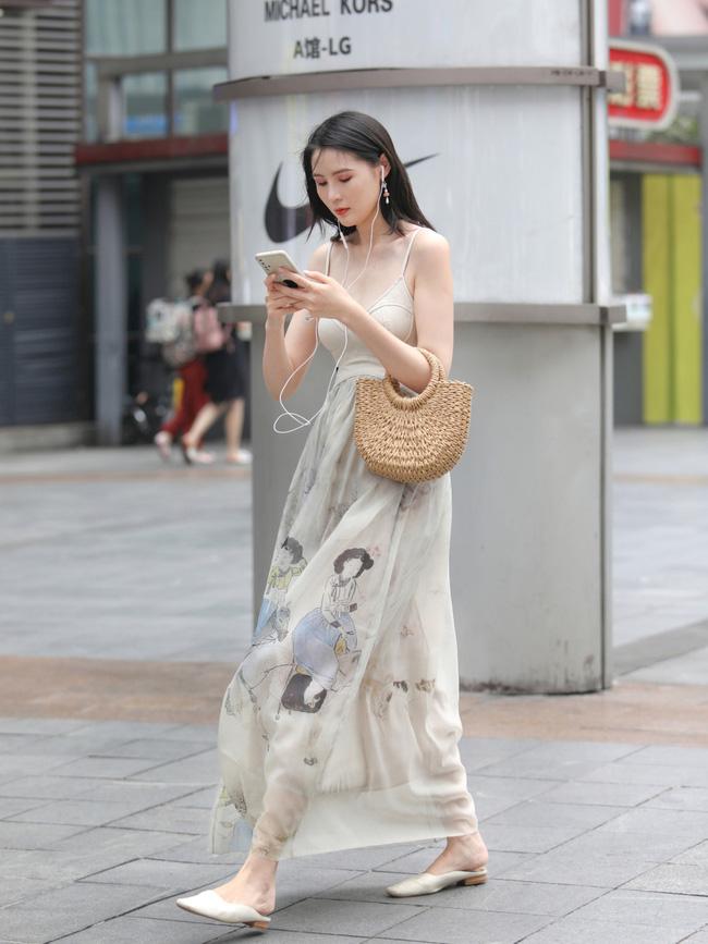 Cô nàng này lựa chọn cho mình chiếc váy hai dây với màu sắc basic, phần chân váy được in họa tiết bắt mắt. Thêm túi xách cói và loafer cùng tone với váy.
