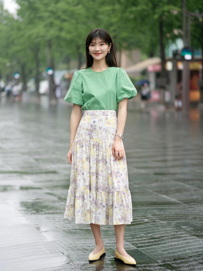 Chiếc áo blouse tay bồng màu xanh mướt mắt, nàng này lại chọn cách tạo điểm nhấn bằng chân váy midi hoa và một đôi giày mũi nhọn.