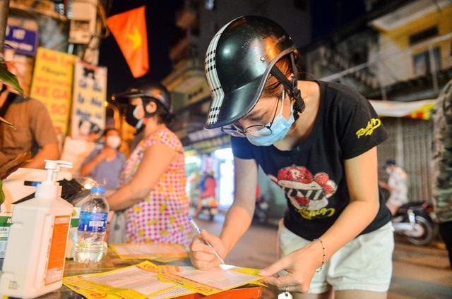 Người dân xem menu danh sách các loại bánh của cửa hàng và ghi những thông tin từng loại bánh cần mua (Ảnh: Người lao động)