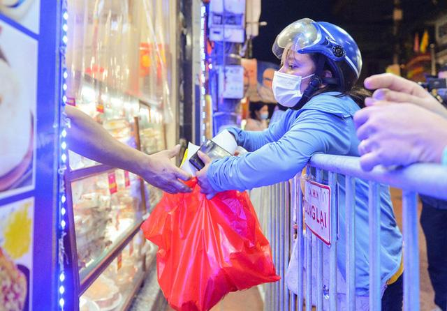 Nhân viên cửa hàng đang đưa bánh chung thu qua lớp vách ngăn bằng túi nilon cho người dân (Ảnh: Người lao động)