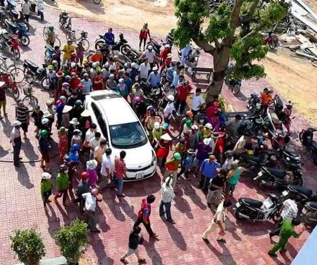Người dân vây quanh chiếc xe ô tô của 2 người bị tình nghi bắt cóc trẻ em