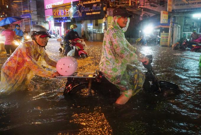 Nước ngập gần hết bánh xe khiến những người điều khiển xe máy chỉ có thể đẩy cố qua dòng nước ngập
