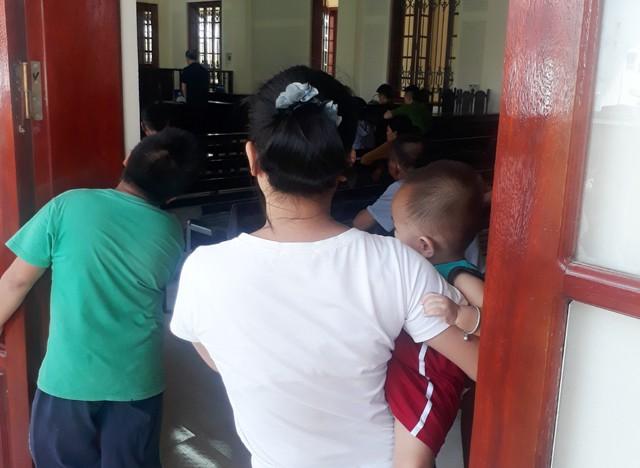 Vì quy định trẻ em không được vào tòa, Loan đành bế con ngóng vào bên trong nghe xét xử