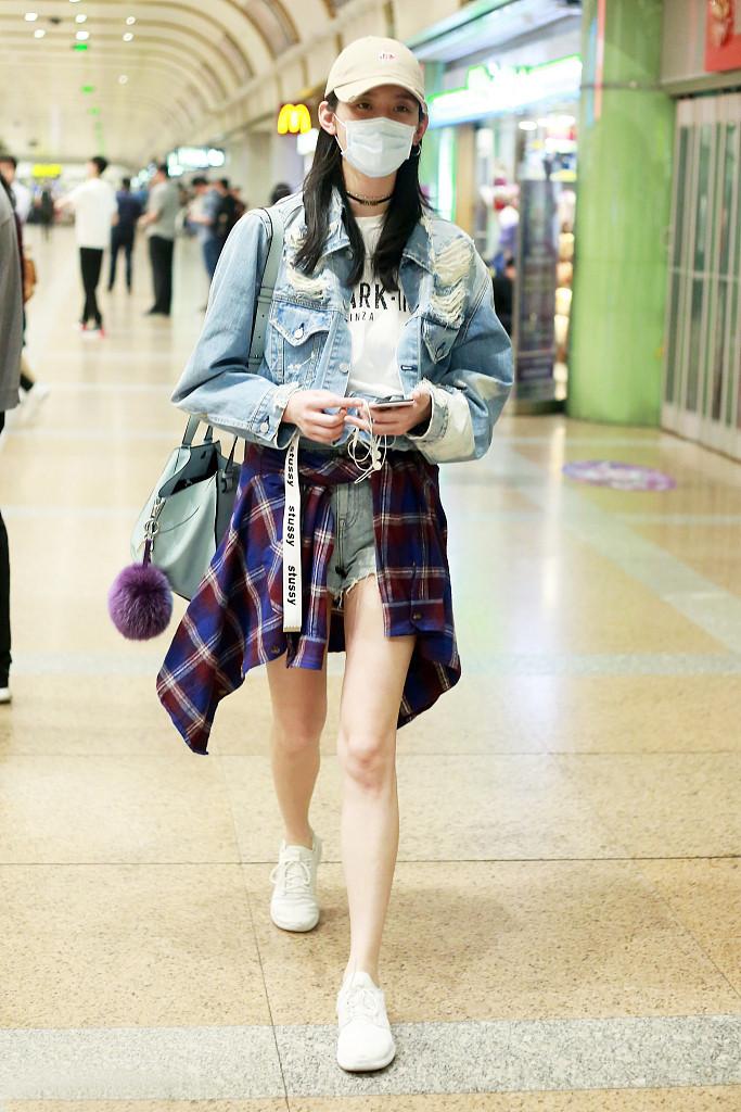 Quần short jean mặc cùng áo thun, denim jacket, buộc áo sơ mi giữa eo tạo nên set đồ năng động cho Hề Mộng Dao.